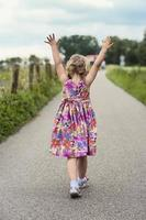 peuter lopen met haar handen omhoog in de lucht foto