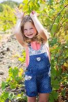 kindmeisje dat pret in druivenwijngaard heeft foto