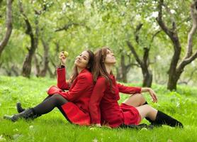 twee vrouwen zitten op gras foto