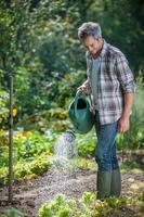 portret van een tuinman die zijn tuin water geeft foto