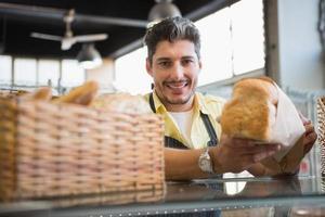 vrolijke werknemer permanent en presenteren een brood foto