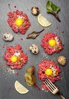 tartaar van rundvlees met ei, kappertjes en uien op donkere achtergrond foto