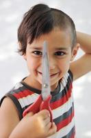 kind haar knippen zichzelf met een schaar, grappige look foto