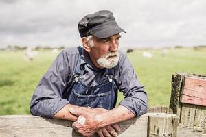 bejaarde boer onderzoekt zijn landbouwgrond