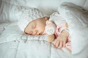 lieve kleine baby slaapt met een stuk speelgoed foto