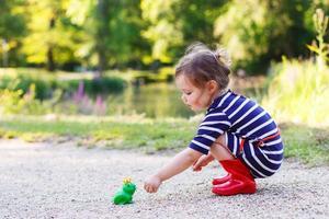 schattig prinses meisje in regenlaarzen spelen met rubber speelgoed foto