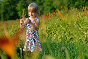 klein meisje op de weide van bloemen. foto