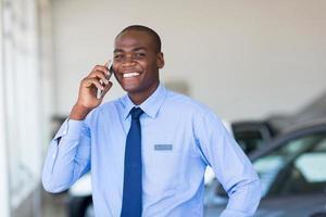Afro-Amerikaanse autoverkoper praten op mobiele telefoon foto
