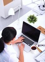 aantrekkelijke zakenvrouw zittend op bureau in het kantoor foto