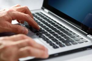 close-up van mannelijke handen typen op laptop toetsenbord foto