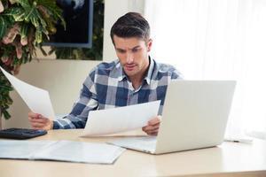 man aan het werk met rekeningen thuis foto