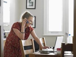 vrouw op afroep met behulp van laptop in de eetkamer foto