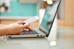 drukke jonge vrouw typt op laptopcomputer en gebruikt foto