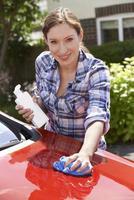 portret van vrouw waxen auto buiten huis foto