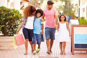 familie wandelen langs de straat met boodschappentassen foto