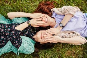 twee vrolijke zussen liggend op het gras foto