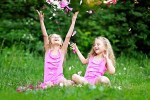 portret van twee tweelingen met pioenrozen foto