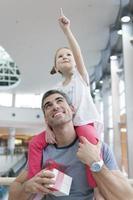 jonge dochter wijst en zit op vaders schouders foto