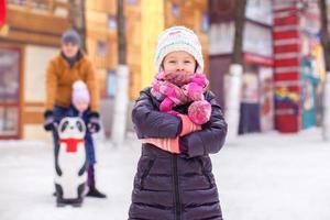 charmant meisje op ijsbaan, vader met kleine zusje achtergrond