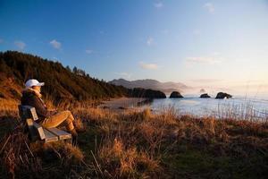 vrouw op bankje met uitzicht op kust foto