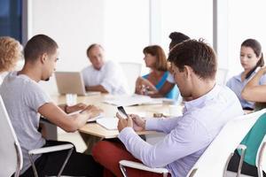 zakenman die mobiele telefoon in bestuurskamervergadering met behulp van foto