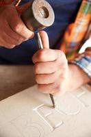 close up van stenen metselaar bezig met snijwerk in studio