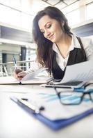 zakenvrouw het maken van aantekeningen op haar bureau foto