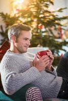 kerstochtend, man met een kopje in de buurt van de kerstboom foto