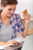 lachende vrouw online winkelen met behulp van computer en creditcard in foto