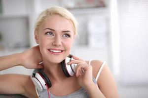 jonge mooie vrouw die thuis op bank zit en luistert foto