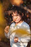 dromerig meisje houdt grasspriet bij de neus foto