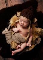 pasgeboren babyjongen met een aap hoed foto