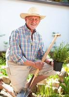 senior tuinman met een schop foto
