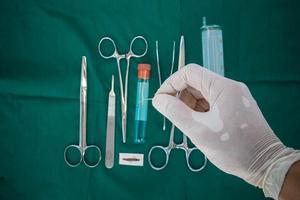 hand met haak voor hechtdraad, met instrumenten voor chirurgieachtergrond foto