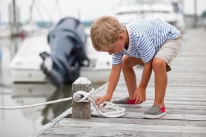 de jonge jongen bindt knoop op bootdok foto