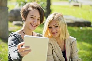 twee mooie jonge vrouwen die tablet buiten doorbladeren. foto