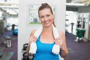 fit brunette lachend op camera in fitness-studio