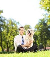 man zittend op een gras en knuffelen zijn labrador hond foto