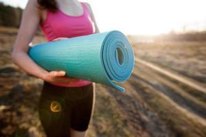 vrouw lopen met een yogamat buiten tijdens zonsondergang foto