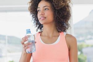 passen vrouwelijke fles water houden op sportschool foto