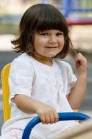 schattig klein meisje op schommel in de speeltuin foto
