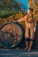 portret van een jonge vrouw in de buurt van houten vat in de herfst buiten foto