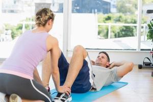 trainer helpen fit man bij het doen zit foto