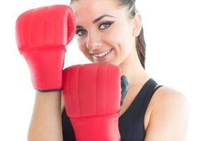 aantrekkelijke sportieve vrouw die lacht op camera bokshandschoenen dragen foto