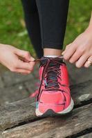 sluit omhoog van jonge vrouw die haar schoenveters bindt foto