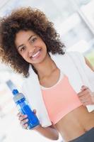 passen jonge vrouwelijke bedrijf fles water op sportschool foto