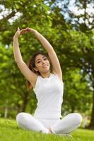gezonde vrouw die zich uitstrekt handen in park foto