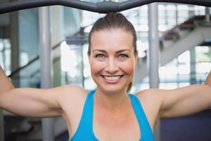 fit brunette met behulp van gewichten machine voor armen