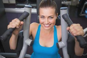 fit brunette met behulp van gewichten machine voor armen foto