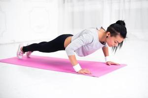 jonge Latijns-vrouw warming-up en doet push-ups op foto